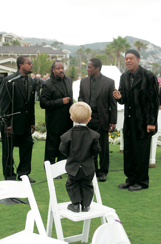 ring-bearer-stands-on-chair-to-look-at-ceremony-musicians