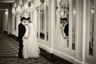 black-and-white-photo-of-couple-in-mirror-and-hallway