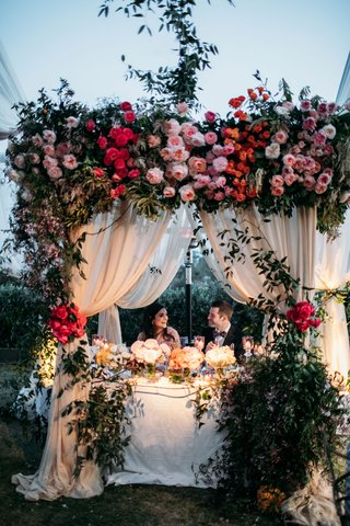wedding reception sweetheart table under ceremony structure pink flowers greenery drapery