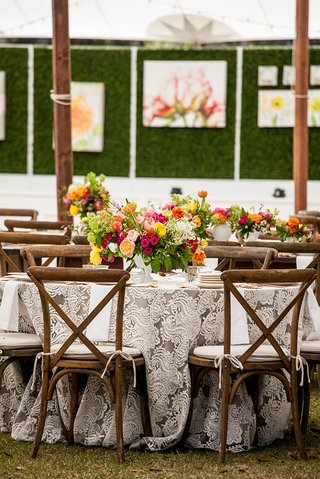 outdoor-wedding-wood-chairs-rustic-bright-centerpiece-yellow-pink-green-orange-flowers-lacy-linen