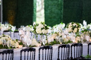 wedding reception black chairs white linen ivory flowers greenery classic timeless wedding centerpiece tablescape