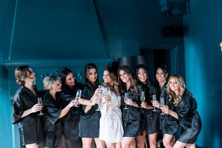 bridesmaids-in-black-satin-robes-with-champagne-glasses-cheers-bride-in-white-robe-bridesmaid-photos