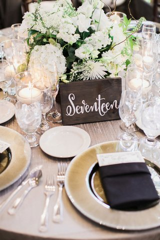 dark-rectangular-piece-of-wood-with-white-calligraphy-for-wedding-table-number