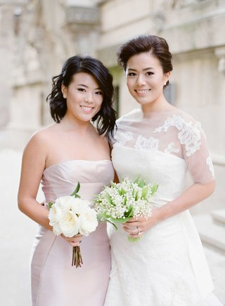 bride-in-vera-wang-wedding-dress-lily-of-the-valley-bouquet-and-maid-of-honor-bridesmaid-with-roses
