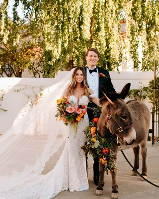 bride and groom with donkey at wedding spanish style details orange pink flowers