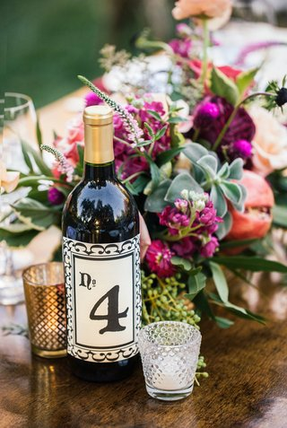 outdoor-bohemian-wedding-reception-table-with-table-number-on-wine-bottle-label-votive-candles