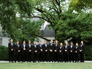 country club wedding large bridal party groomsmen tuxedos bow ties white boutonniere flowers