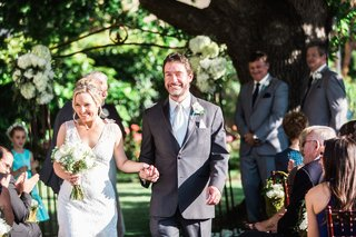 bride-in-a-sleeveless-claire-pettibone-dress-walks-with-groom-in-grey-suit-after-a-garden-ceremony