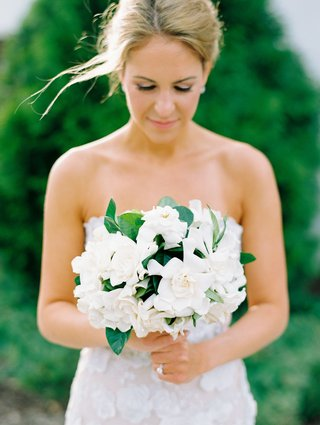 bride with hair pulled back holding bridal bouquet gardenia flowers