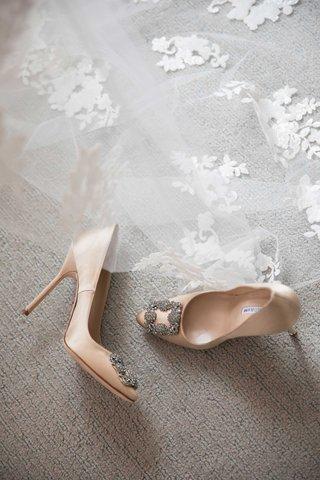 manolo-blahnik-nude-wedding-heels-with-crystal-buckle-detail-at-toe-pumps-ceil-with-flowers