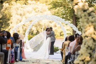 bride-and-groom-kiss-under-white-flower-arches-outdoor-garden-ceremony-ghana-royalty-africa-wedding