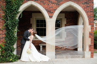 bride-and-groom-kiss-as-cathedral-veil-floats-in-wind