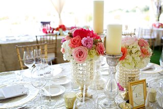 wedding-reception-table-with-pink-and-white-flowers-in-beaded-vases-and-pillar-candles