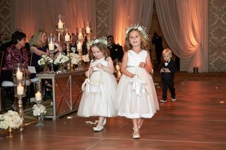 flower-girls-walking-down-aisle-with-ring-bearer-behind-babys-breath-flower-crowns-white-dresses