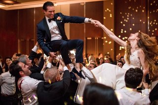 wedding-reception-bride-and-groom-on-chairs-during-hora-dance-jewish-wedding-reception