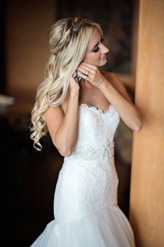 bride-with-blonde-hair-putting-on-earrings