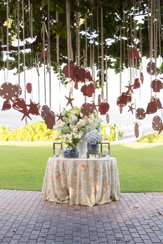 cocktail-hour-decor-table-with-seashell-starfish-shaped-escort-cards-hanging-from-tree-by-ocean