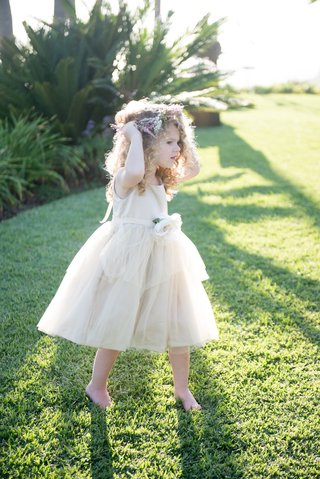 flower-girl-in-an-off-white-dress-with-straps-ribbon-belt-with-large-white-flower-tulle-skirt