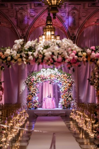 gold-and-white-checker-floor-candlelight-lush-pink-orange-white-flower-arch-with-chandelier