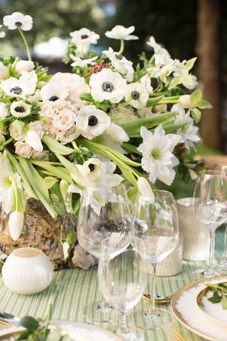 green-and-white-floral-centerpiece-arrangement-in-tree-stump-vase-green-linens-white-candles