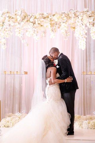 wedding-ceremony-bride-groom-kiss-mermaid-wedding-dress-white-orchid-hydrangea-rose-on-lucite-arbor