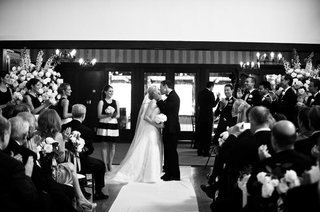 black-and-white-photo-of-bride-in-a-strapless-vera-wang-dress-veil-kisses-groom-in-a-black-tuxedo