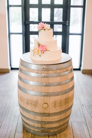 white-wedding-cake-with-ivory-and-pink-peonies-on-a-wood-barrel