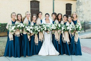 bride-in-romona-keveza-wedding-dress-with-fur-wrap-and-bridesmaids-in-navy-blue-with-champagne-throw