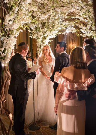 couple-getting-married-by-jewish-rabbi-under-a-chuppah-made-of-foliage-and-white-flowers