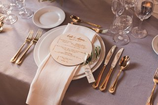 wood-round-circle-menu-card-on-plate-with-name-tag-wrapped-to-olive-tree-sprig
