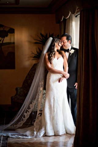 cathedral-length-veil-sweetheart-neckline-gown-portrait-of-bride-and-groom-by-window