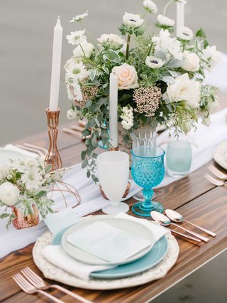 blue-and-white-tablescape-featuring-rose-gold-and-green-accents-in-the-candles-floral-arrangement