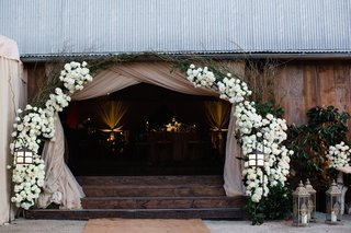 wedding-reception-barn-entrance-with-white-flowers-arch-tan-drapery-steps-up-lanterns