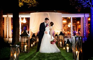 bride-and-groom-wedding-portrait-in-front-of-tent-reception-area-lanterns-and-drapery