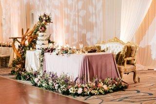 wedding-reception-ballroom-sweetheart-table-gold-antique-settee-purple-linen-greenery-driftwood-cake