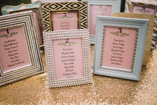 mismatched-frames-with-pink-seating-charts-for-tables