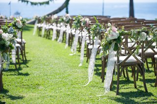 oceanfront-wedding-with-pink-peach-white-flowers-greenery-lace-on-wood-chairs-along-aisle