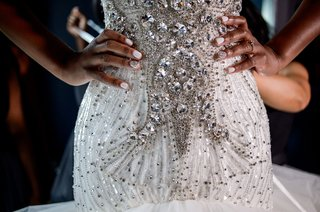 bride-in-form-fitting-drop-waist-wedding-dress-jewel-beads-white-manicure-nails-with-rhinestones