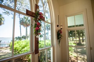 wood-cross-on-arch-window-of-chapel-montage-palmetto-bluff-yellow-and-pink-flowers-with-greenery