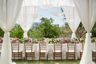 long-table-with-white-linen-pink-flower-table-runner-drapery-and-parasols-at-private-home