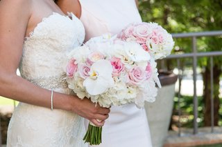 bride-in-strapless-lace-wedding-dress-holding-bouquet-white-orchid-pink-rose-white-hydrangea-flowers