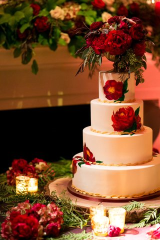 white-wedding-cake-with-gold-leaf-details-and-painted-red-peonies-with-gold-footed-vase-peony-topper