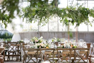 industrial-chairs-and-vineyard-x-back-chairs-around-wood-table-greenery-low-centerpiece-greenhouse