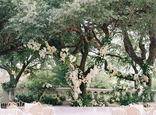 wedding reception stage with flower print gold lace chairs white flowers climbing up trees property