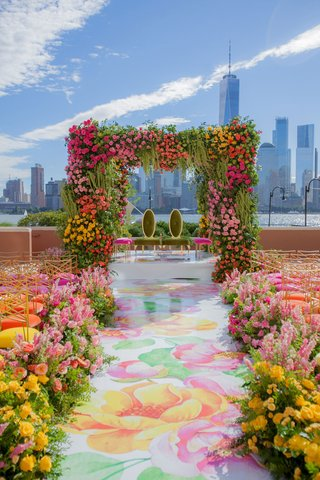 wedding-ceremony-new-york-city-skyline-pink-yellow-green-flower-print-aisle-chairs-mandap