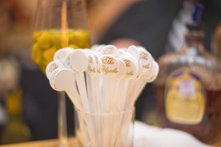 wedding-reception-bar-with-a-glass-of-white-stirrers-bearing-the-couples-surname-in-gold