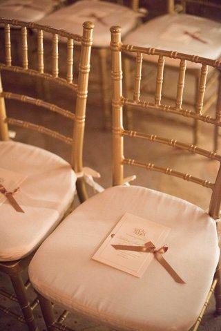 wedding-ceremony-gold-chairs-white-cushions-monogram-ceremony-program-gold-ribbon