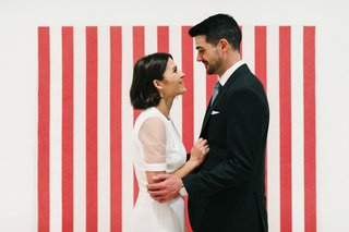 bride-and-groom-in-front-of-white-red-stripe-backdrop