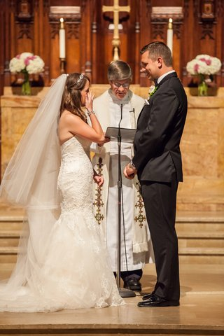 bride-and-groom-standing-with-pastor-in-chapel