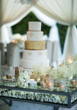 white-and-gold-wedding-cake-on-crystal-table-white-flower-bouquets-champagne-flutes